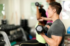 Young man lifting free weights in the gym.