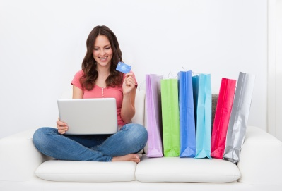 Young Woman Shopping Online Sitting Besides Row Of Shopping Bags